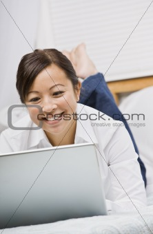 Attractive Asian Woman Lying Down with Laptop