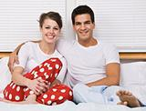 Smiling Couple Sitting in Bed
