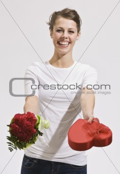 Attractive Young Woman Holding Out Roses and Candy