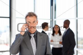 Mature businessman on phone looking at the camera