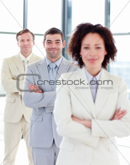 Attractive businessman with folded arms in a row