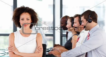 Attractive businesswoman with folded arms in a call center
