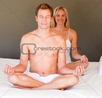 Young couple doing spiritual exercises on bed