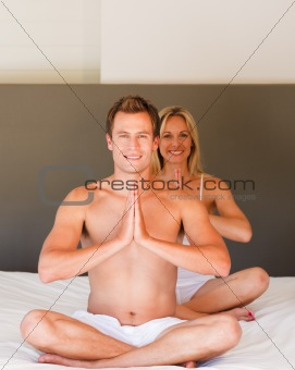 Young couple doing yoga moves on bed