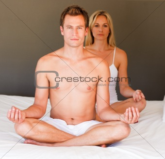 Couple doing meditating on bed