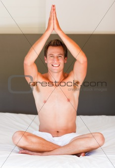 Handsome man meditating on bed smiling at the camera