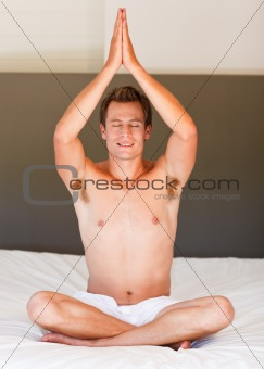 Smiling boy doing yoga on bed