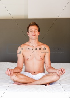 Handsome man doing meditation on bed