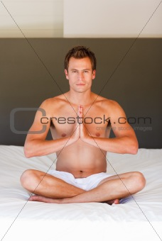 Young boy doing exercises on bed