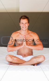 Smiling man meditating on bed