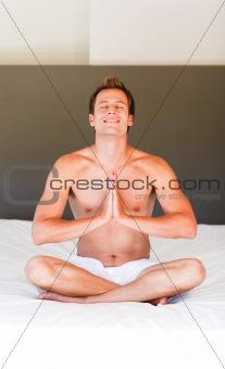 Attractive man meditating on bed