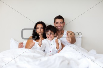 Little boy with thumbs up and his parents in bed