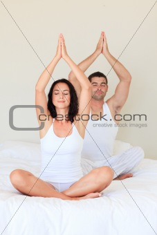 Couple doing exercises on bed with closed eyes
