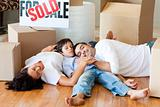 Happy family moving house lying on floor