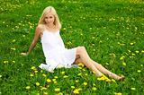 Young woman relaxing on a green meadow with dandelion