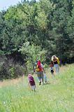 Happy family hiking through the summer meadow to the wood.
