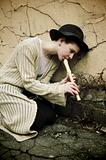 Young girl in a hat playing flute