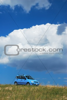 Bright pale blue modern car under white cloud and blue sky