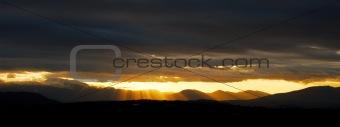 Bright sun beams bursting through very dark threatening clouds