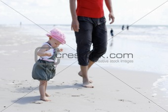 A little girl with her father at the beach.