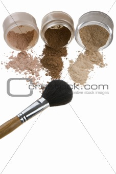 Cosmetics and brushes for a make-up on a light background