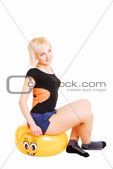 a young woman in for fitness sits on the big yellow  ball and lo