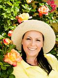 smiling woman in hat staying in the garden