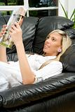 Female model relaxing on sofa reading magazine