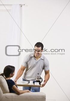 Attractive man serving a tray of food to a woman.