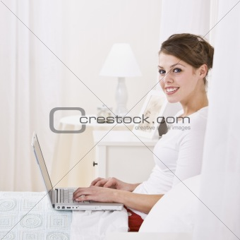 Attractive Woman Relaxing in Bed with a Laptop