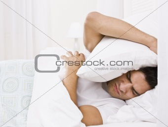 Tired Man Hiding His Head with Pillow