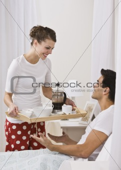 Attractive woman serving breakfast in bed.