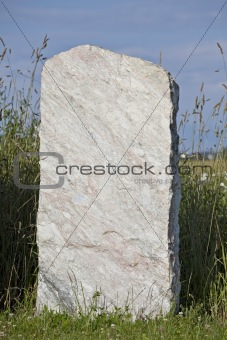 single empty granite gravestone on a grass meadow