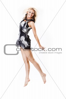 Smiling young female in dress jumping