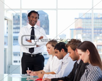 Afro-American manager with folded arms working with his team