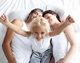 Happy little girl on bed with her parents