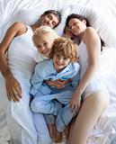 Family sleeping in pqrent's bed
