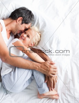 Father huggling her daughter on bed