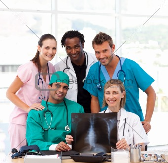 Medical team examining an X-ray and smiling at the camera
