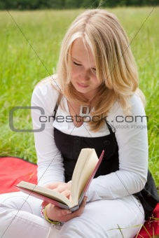 Pretty young girl reading a book