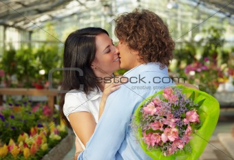 couple kissing in flower nursery