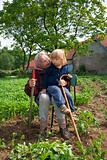grandmother with her grandson sitting together on chair in potato field