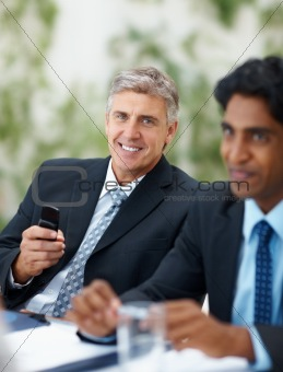 Happy senior business man holding his cell phone