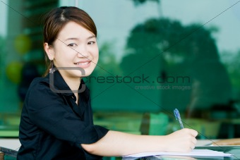 Asian business woman writing report