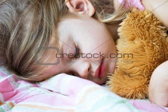 Toddler sleeping with her teddy bear