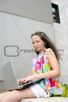 Beautiful brunette teen little girl laptop city