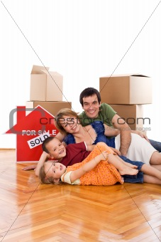 Happy family laying on the floor of their new home