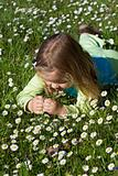 Little girl laying among little wildflowers