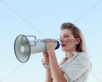 Blonde businesswoman shouting through megaphone