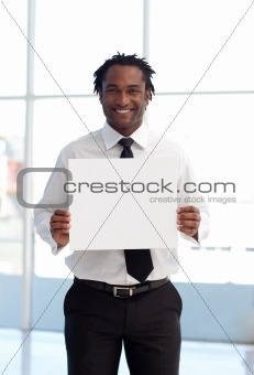 Smiling Afro-American businessman holding a white card
